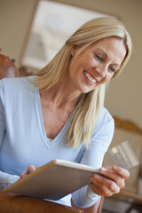 Smiling woman holding credit card and digital tablet