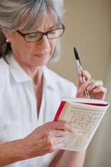 Close up of senior woman holding sudoku book and pen