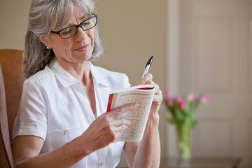 Senior woman holding sudoku book and pen