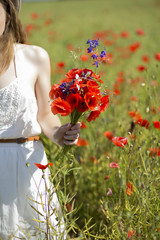 Woman at white dress and scarlet bouquet