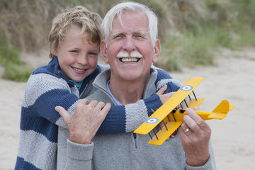 Grandfather And Grandson Playing With Model Aeroplane On Beach