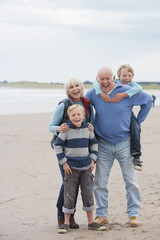Grandparents And Grandchildren Walking Along Beach Together