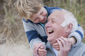 Grandson Hugging Grandfather In Sand Dunes