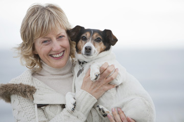Mature Woman Walking Along Beach With Dog