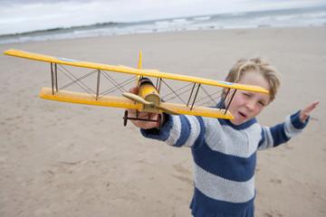 Boy Playing With Model Aeroplane On Beach