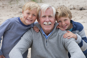 Portrait Of Grandfather And Grandsons On Beach