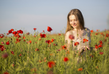 Woman at white dress walk between poppies