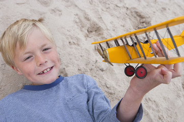 Boy Playing With Model Aeroplane On Beach