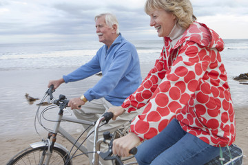 Mature Couple Riding Cycles On Winter Beach Holiday