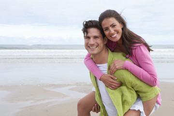 Man Giving Woman Piggyback Along Summer Beach