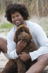 Portrait Of Man Sitting On Winter Beach With Dog