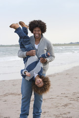 Father And Son Playing On Winter Beach