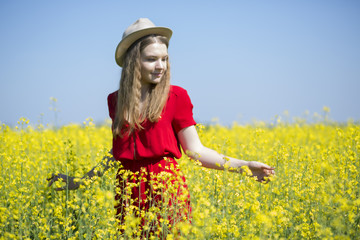 Woman at red dress between yellow plants