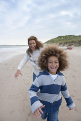 Mother Chasing Son Along Winter Beach