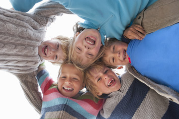 Group Of Excited Children Looking Down Into Camera