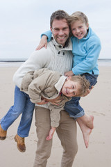 Father Carrying Children Along Beach