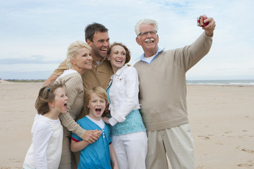Taking Photo Of Multi Generation Family On Beach Holiday