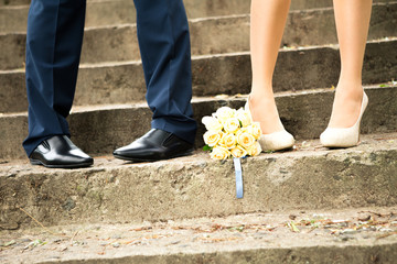 legs of groom and bride and bouquet