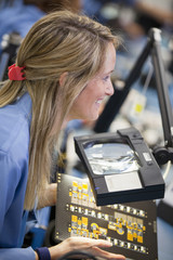 Close up of smiling technician examining printed circuit board in hi-tech electronics manufacturing plant