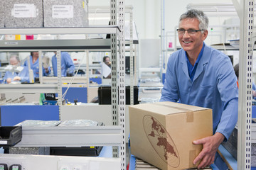 Smiling worker lifting cardboard box from conveyor belt in factory
