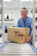 Smiling worker placing cardboard box on conveyor belt in factory