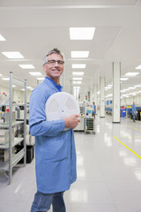 Portrait of smiling engineer holding data tape in hi-tech manufacturing plant