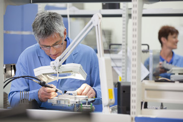 Technician working on assembly line in hi-tech electronics manufacturing plant