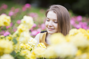 Happy woman surrounded by many yellow roses