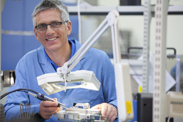 Portrait of smiling technician working on assembly line in hi-tech electronics manufacturing plant