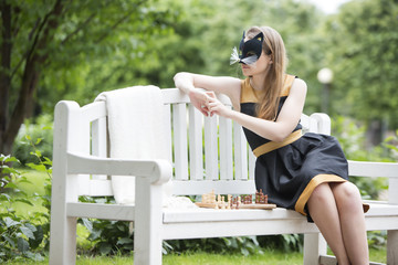 Woman  with mask and costume on bench