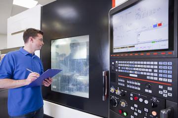 Technician with clipboard watching lathe cutting machine in hi-tech manufacturing plant