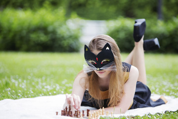 Woman  with mask adjust wooden chess pieces