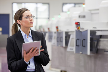 Businesswoman with digital tablet looking up in hi-tech manufacturing plant