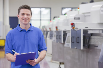 Portrait of smiling technician holding clipboard in hi-tech manufacturing plant