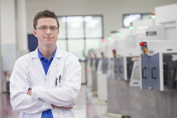 Portrait of smiling scientist with arms crossed in hi-tech manufacturing plant