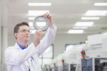 Scientist examining gear wheel in hi-tech manufacturing plant