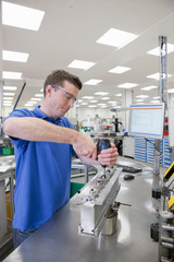 Technician assembling product in hi-tech manufacturing plant