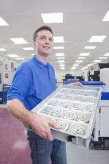 Technician holding tray of aluminum products in hi-tech manufacturing plant