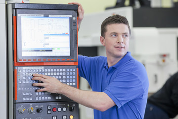 Technician controlling lathe cutting machine in hi-tech manufacturing plant
