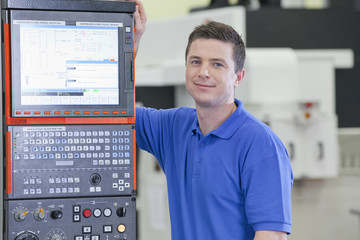 Portrait of smiling technician leaning on lathe cutting machine