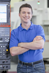 Portrait of smiling technician leaning against lathe cutting machine in hi-tech manufacturing plant