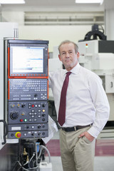 Portrait of confident businessman leaning against lathe cutting machine in hi-tech manufacturing plant