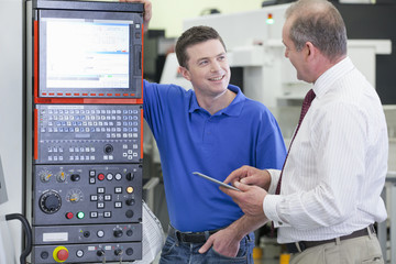 Technician and businessman with digital tablet at lathe cutting machine in hi-tech manufacturing plant