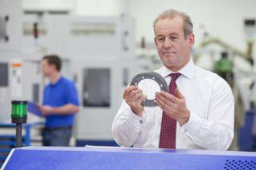 Businessman examining gear wheel in hi-tech manufacturing plant
