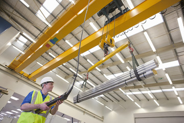 Technician operating hoist with raw aluminum in hi-tech manufacturing plant