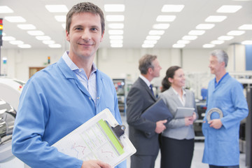 Portrait of smiling engineer with clipboard in machine part manufacturing plant