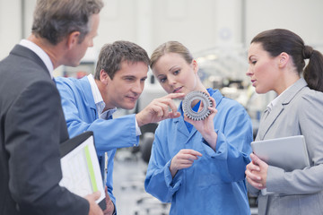 Business people and engineers discussing machine part in manufacturing plant