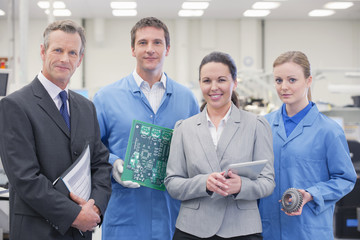 Portrait of confident business people and engineers with printed circuit board and machine part in manufacturing plant