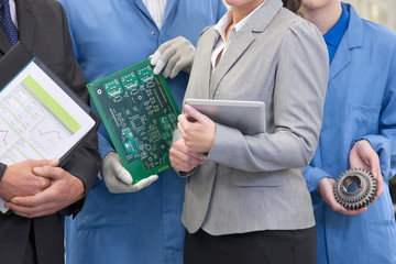 Close up of business people and engineers with printed circuit board and machine part in manufacturing plant