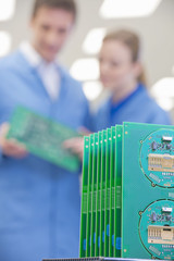 Close up of printed circuit boards with engineers in background